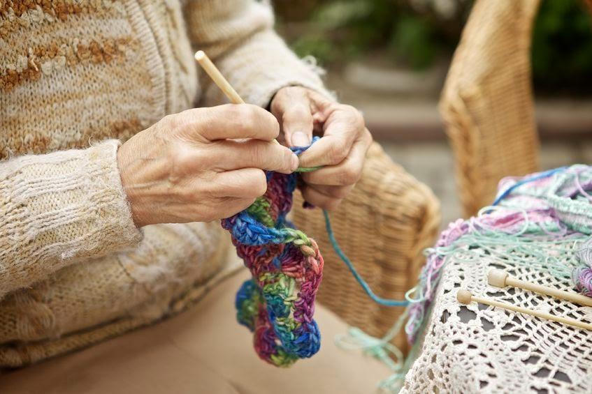 Starsza pani robiąca na drutach